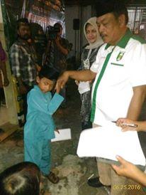 Yusfar sedang Menyantuni Anak Yatim yang didampingi Istri . (foto.Mi)