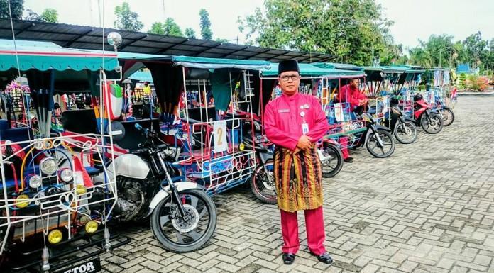 Ismail Arsyad, Sekretaris dinas Pariwisata Meranti bersama Becak yang di hias. (foto:fb)