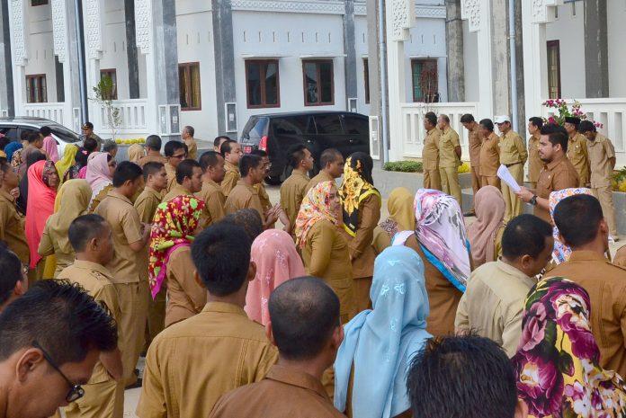 SEKDA Aceh Timur, M. Ikhsan Ahyat (2 kanan) menyalami para PNS usai apel hari pertama masuk kerja di halaman Kantor Setdakab Aceh Timur, Senin (3/7/2017). Foto: Humas Aceh Timur