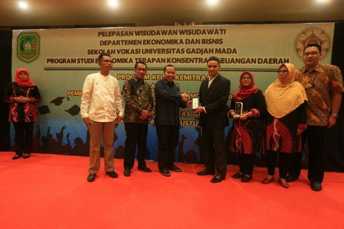Bupati Irwan didampingi ketua DPRD Meranti dan kadisdik Meranti saat menyerahkan cendera mata di UGM