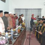 Kadis Syariat Islam Provinsi Aceh mewakili Gubernur Aceh drh. Irwandi Yusuf mengenakan baju toga secara simbolis kepada koordinator dewan Hakim MTQ XXXIII. Foto Bagian Humas Aceh Timur.