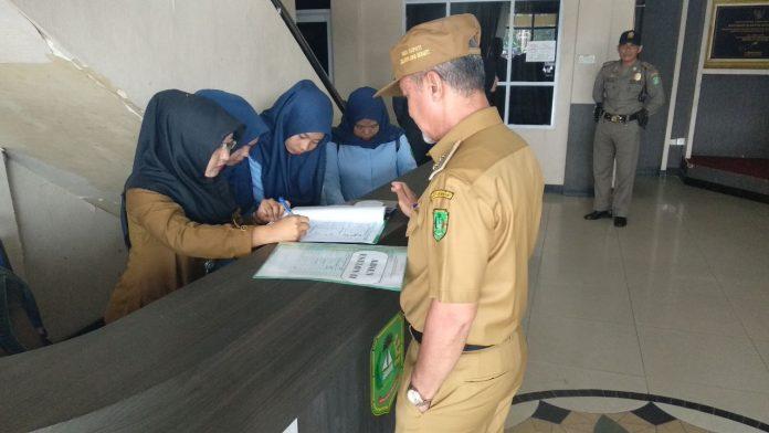 H. Said Hasyim saat mengecek satu persatu absensi pejabat dilingkungan Pemkab. Meranri yang hadir dalam Apel, Senin Pagi, dihalaman Kantor Bupati, (12/3/2018).