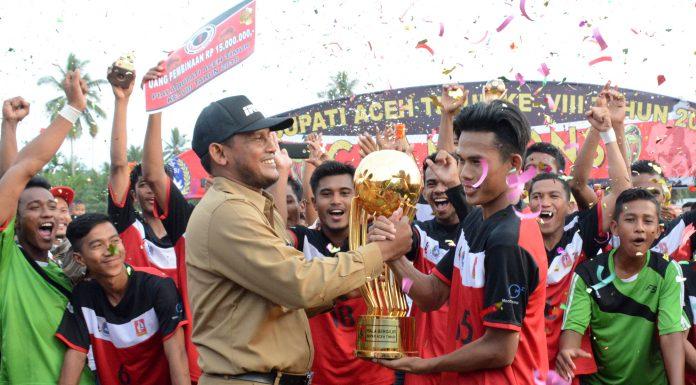Bupati Aceh Timur H. Hasballah HM.Thaib, menyerahkan tropi piala bergilir ke PS. Darul Ihsan. Foto Humas Aceh Timur